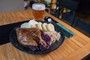 Roast duck, half of duck roasted in lager until golden and served with bread and potato dumplings and red and white cabbage
